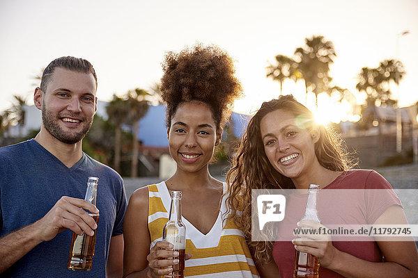 Gruppenbild von drei Freunden mit Bierflaschen am Strand bei Sonnenuntergang