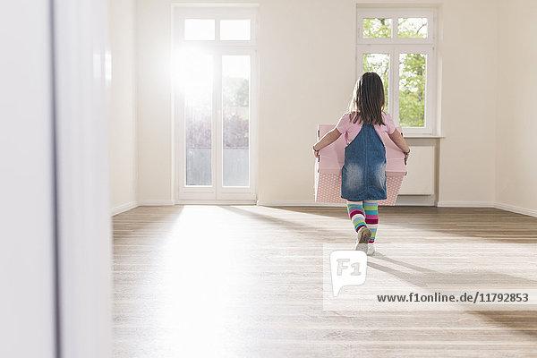 Mädchen mit Pappkarton in leerer Wohnung