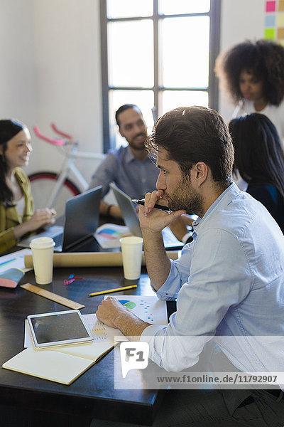 Geschäftsmann  der während einer Besprechung im Büro denkt