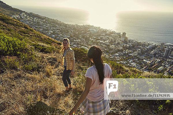 Südafrika  Kapstadt  Signal Hill  zwei junge Frauen beim Wandern über die Stadt