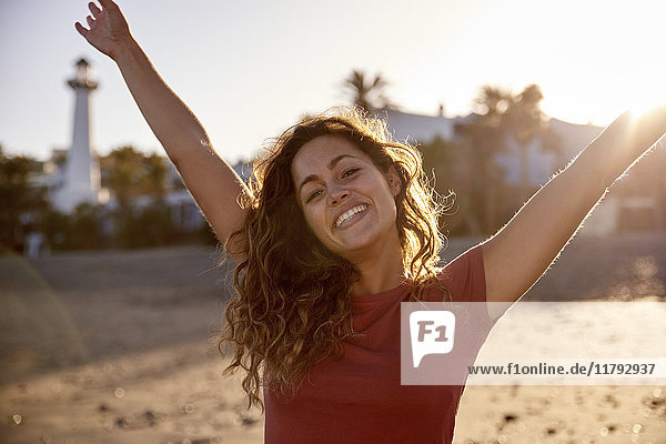 Spanien  Kanarische Inseln  Gran Canaria  Portrait der glücklichen Frau am Strand in der Abenddämmerung
