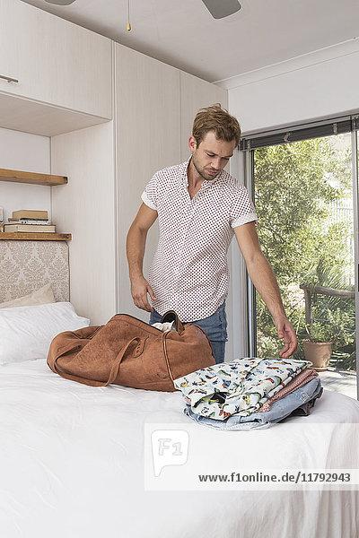 Junger Mann packt Tasche im Schlafzimmer