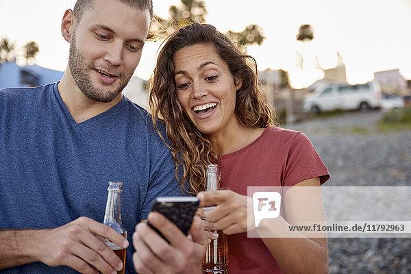 Paar mit Bierflaschen beim Blick auf das Handy am Strand