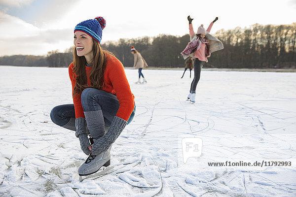 Frau bindet ihre Schlittschuhe auf dem zugefrorenen See.