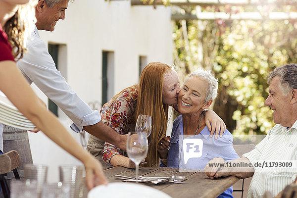 Fröhlicher Familientisch im Freien zum Mittagessen