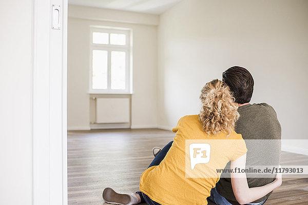 Junges Paar in neuem Zuhause auf dem Boden sitzend