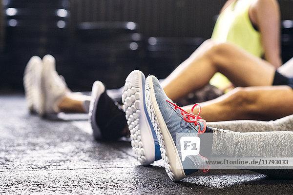 Füße von Sportlern  die in der Turnhalle auf dem Boden sitzen