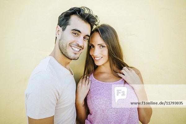 Lächelndes Paar schaut auf die Kamera in der vorderen gelben Wand