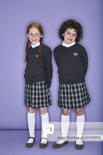 Portrait of two smiling girls wearing school uniform