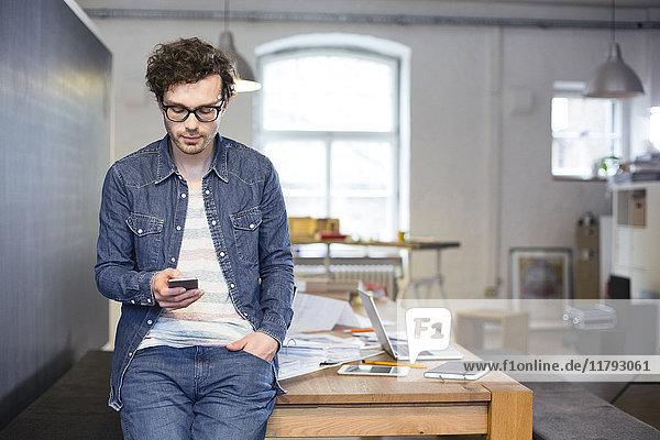 Mann mit Handy im Büro