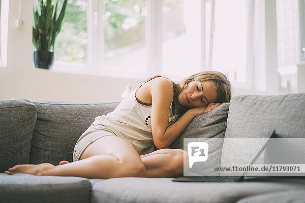 Junge Frau entspannt auf der Couch zu Hause