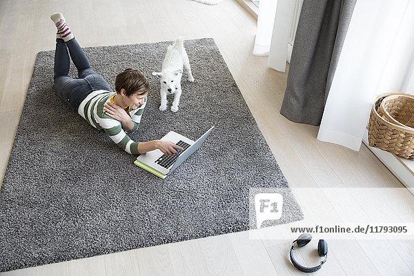 Frau auf dem Boden liegend im Wohnzimmer mit Laptop  während der Hund sie beobachtet.