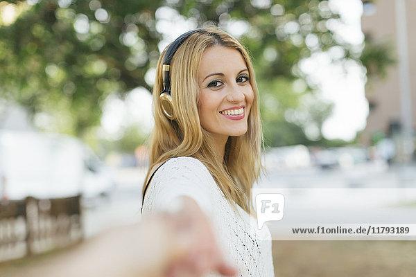 Portrait einer lächelnden blonden Frau mit Kopfhörer