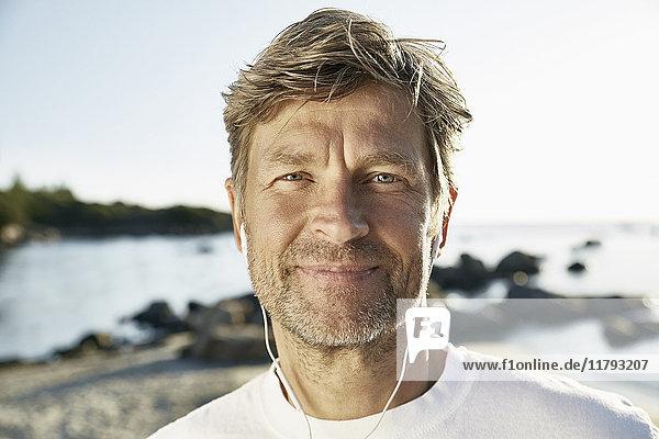 Porträt eines selbstbewussten reifen Mannes mit Kopfhörern am Strand