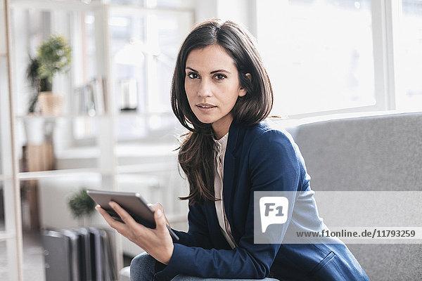 Portrait der Geschäftsfrau mit Tablette auf der Couch