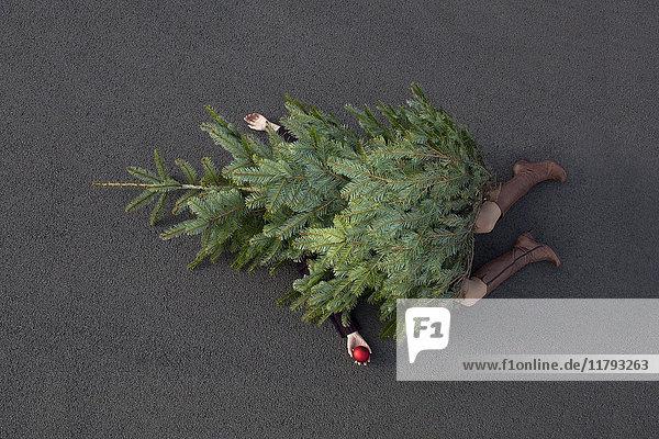 Frau liegt unter dem Weihnachtsbaum begraben