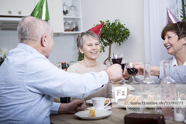 Zwei Seniorenpaare feiern Geburtstag  Toast mit Rotwein