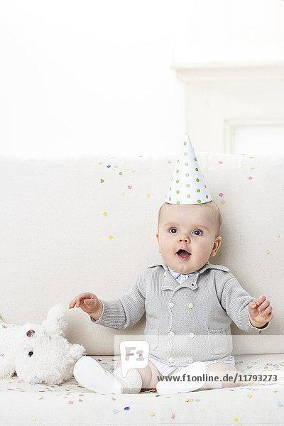 Portrait of amazed baby boy wearing paper hat