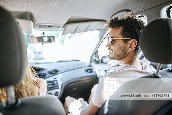 Mann auf dem Beifahrersitz eines Autos mit Blick auf den Fahrer