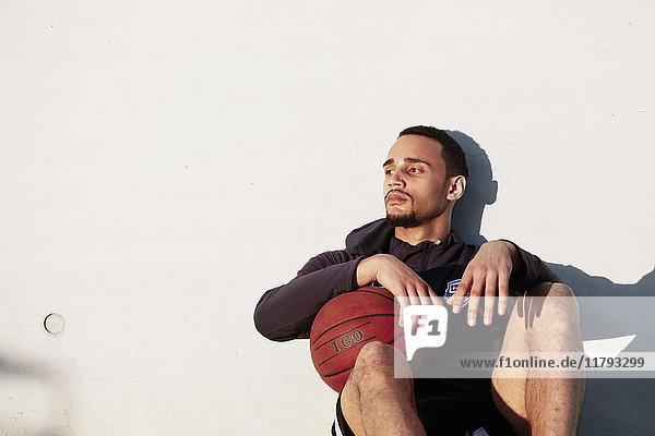 Junger Mann mit Basketball in der Pause