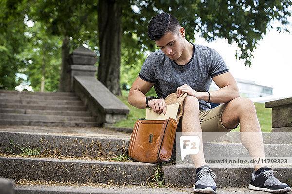 Junger Mann sitzt auf einer Treppe im Park und nimmt Dokumente aus der Tasche.