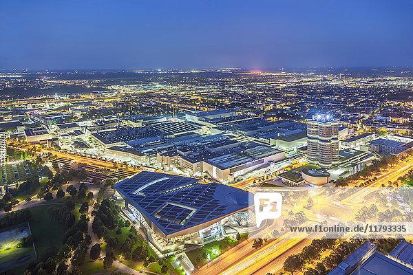 Deutschland  Bayern  München  Stadtbild mit BMW-Hauptsitz in der Nähe des Olympiaparks bei Nacht  Drohnenfotografie