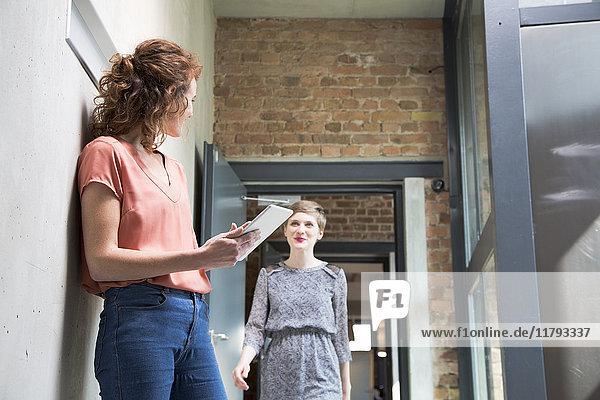 Frau hält Tablette mit Blick auf Kollegin im Hintergrund