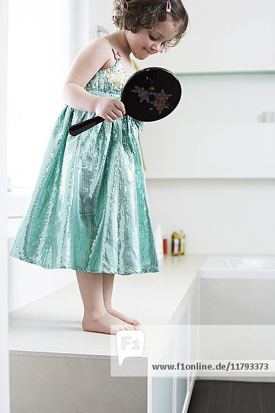 Little girl with hand mirror standing in bathroom looking at her feet