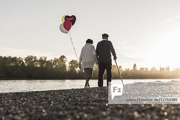 Rückansicht des Seniorenpaares mit Ballons  die abends am Flussufer spazieren gehen.