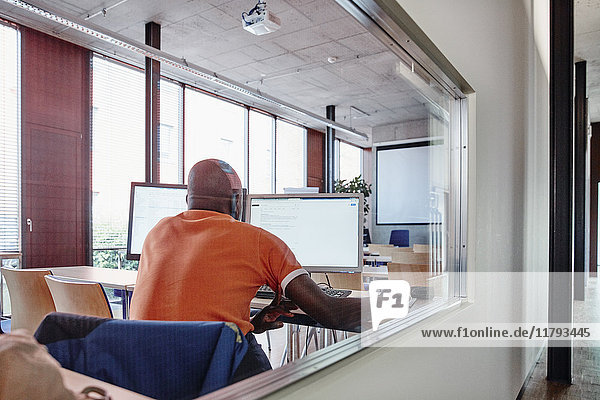 Mann mit Computer im Schulungsraum