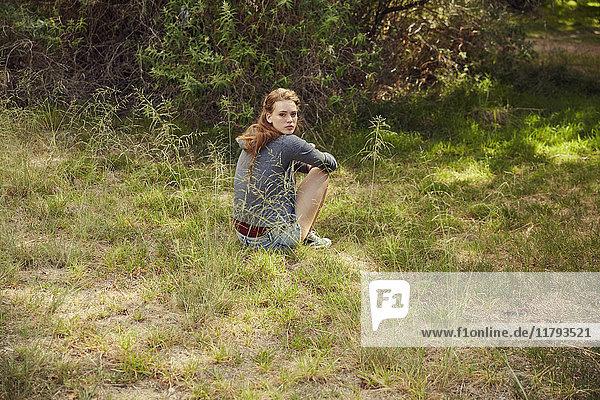Porträt einer jungen Frau auf einer Wiese sitzend