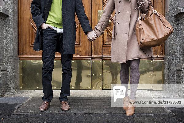 Geschäftsmann und Geschäftsfrau Hand in Hand vor einem Tor
