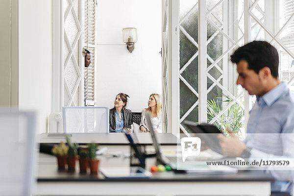 Geschäftsleute sprechen auf dem Balkon  während der Kollege arbeitet.