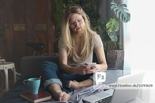 Mann mit langen Haaren und Bart  der auf dem Sofa sitzt und auf das Smartphone schaut.
