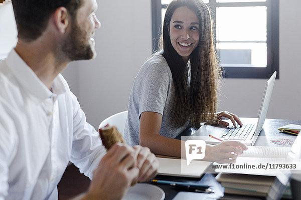 Lächelnde Frau zu Hause mit Laptop und Blick auf Freund