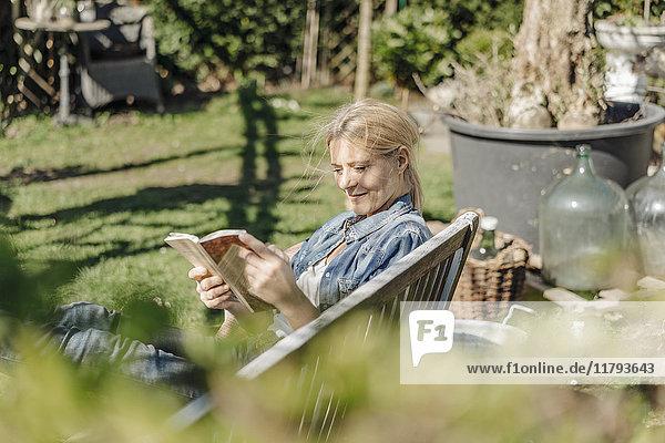 Lächelnde Frau liest Buch auf Gartenbank