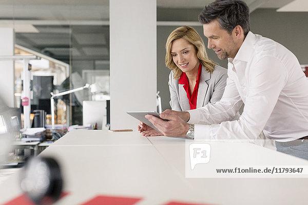Geschäftsmann und Geschäftsfrau bei der gemeinsamen Verwendung von Tabletten