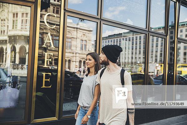 Österreich  Wien  junges Paar  das vor einem Coffee Shop läuft