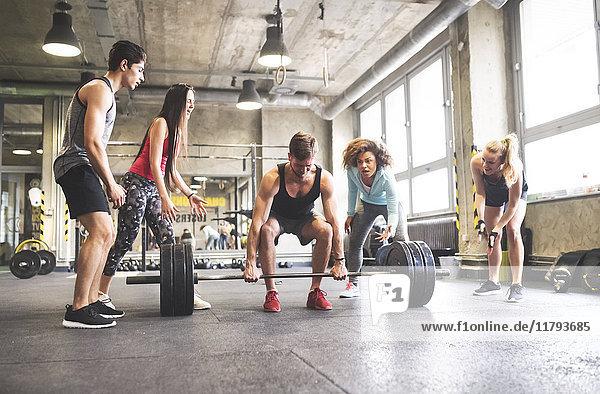 Gruppe von jungen  fitten Menschen  die das Gewichtheben im Fitnessstudio anfeuern