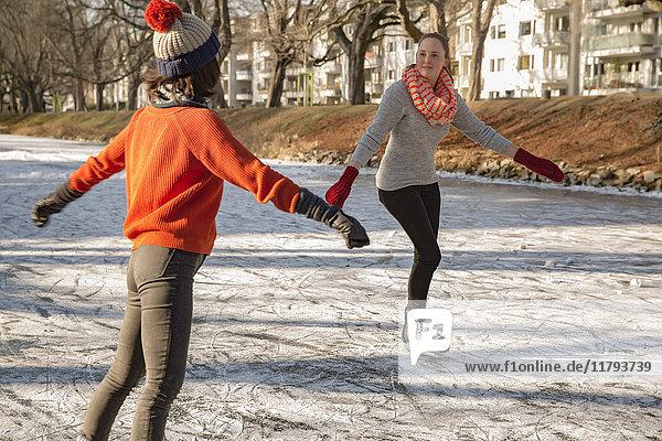 Weibliche Freunde Schlittschuhlaufen auf dem Kanal