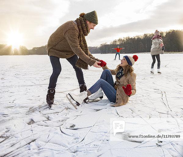 Mann hilft Schlittschuhläuferin auf eisiger Oberfläche des zugefrorenen Sees