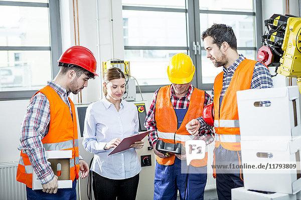 Mitarbeiter diskutieren in der Fabrik mit Industrieroboter im Hintergrund