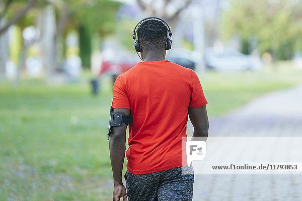 Rückansicht des gehenden Mannes in Sportbekleidung Musik hören mit Kopfhörer