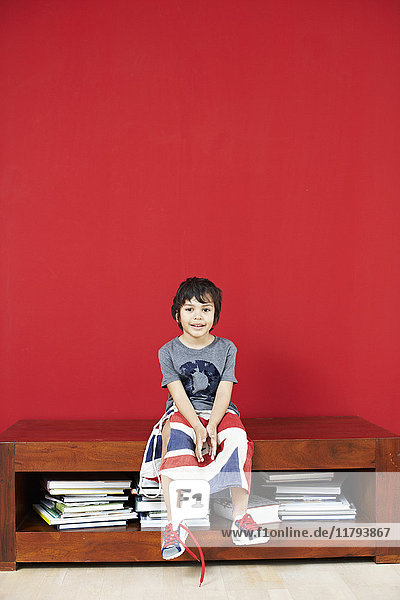 Portrait of little boy sitting on sideboard