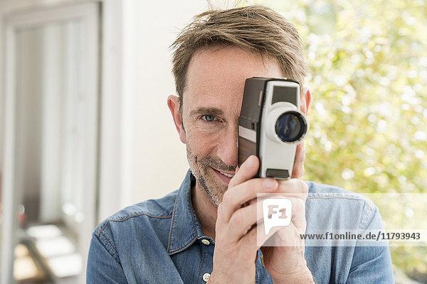 Porträt eines lächelnden Mannes mit Filmkamera beim Betrachter