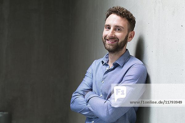 Porträt eines lächelnden Mannes  der sich an eine Betonwand lehnt.