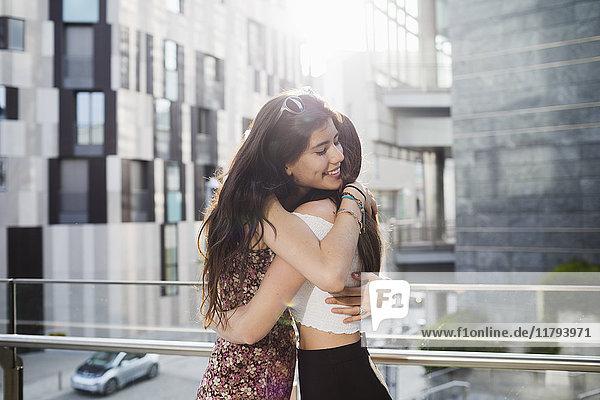 Zwei glückliche junge Frauen  die sich in der Stadt umarmen.