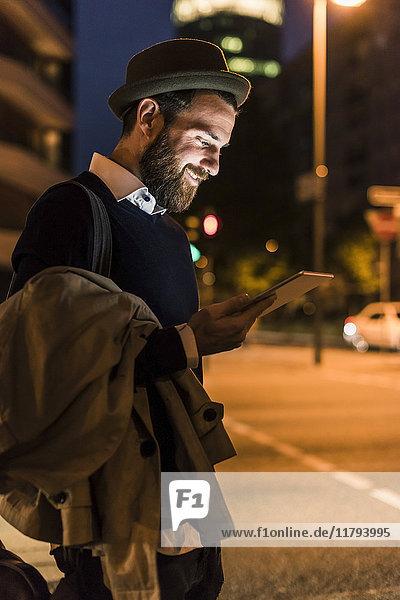 Stilvoller junger Mann mit Tablette auf der Stadtstraße bei Nacht