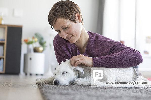 Frau streichelt ihren Hund zu Hause