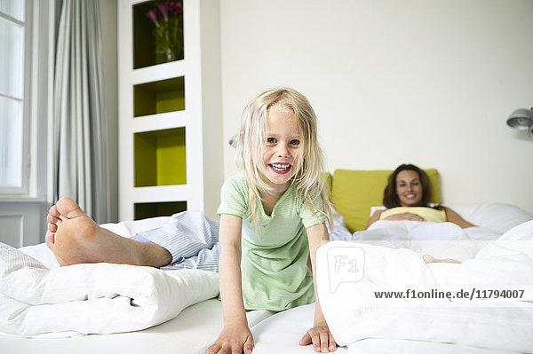 Porträt eines lächelnden kleinen Mädchens im Hotelbett mit ihren Eltern